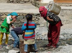 Karshánál a patakból vizet vevő asszony a csládjával